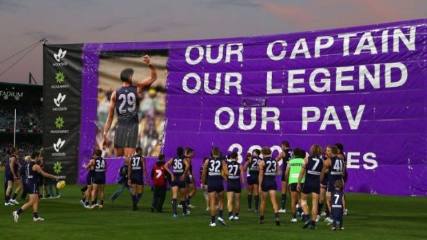 Fremantle players get set to run through an appropriately captioned banner before the game.