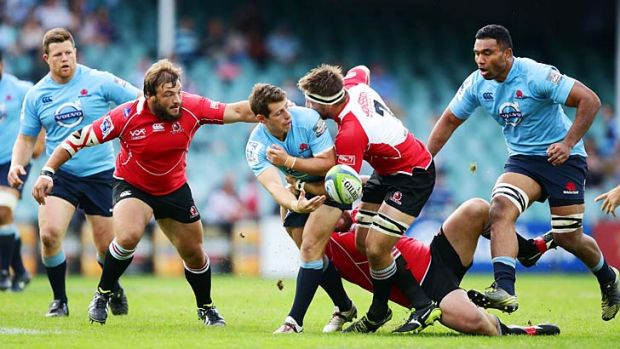 Bernard Foley offloads the ball in a tackle during the match against the Lions on Sunday.