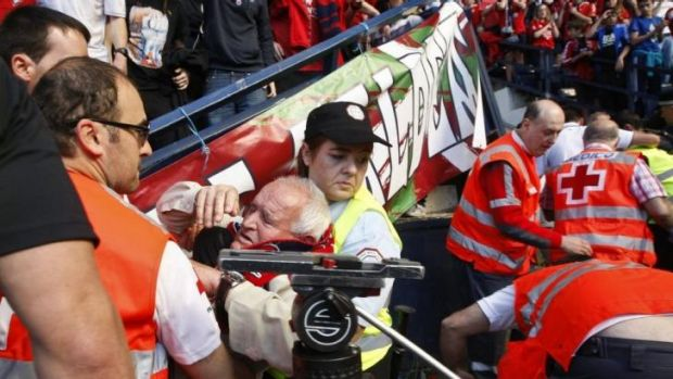 An Osasuna supporter is helped after the barrier collapsed.