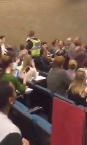 A grainy still from an amateur video shows Sophie Mirabella (right of the man in the yellow vest) after rowdy interjections.
