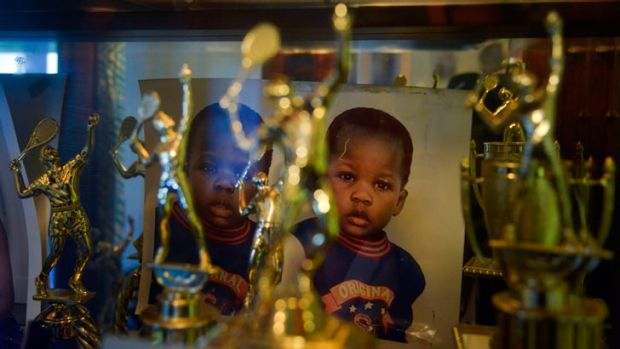 Photographs taken when Franklin and Francis Tiafoe were toddlers sit at the back of a cabinet filled with trophies in ...