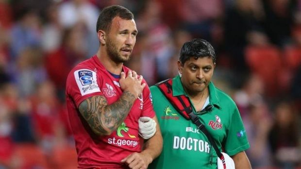 Blow: Reds five-eighth Quade Cooper leaves the field against the Rebels.