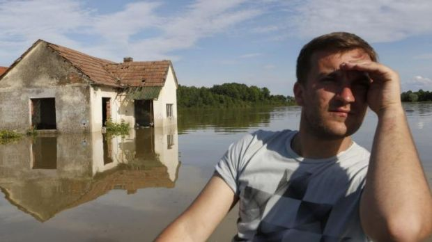 A Bosnian man in a boat searches for people and animals after flooding in the village of Vojskova near the Bosnian town ...