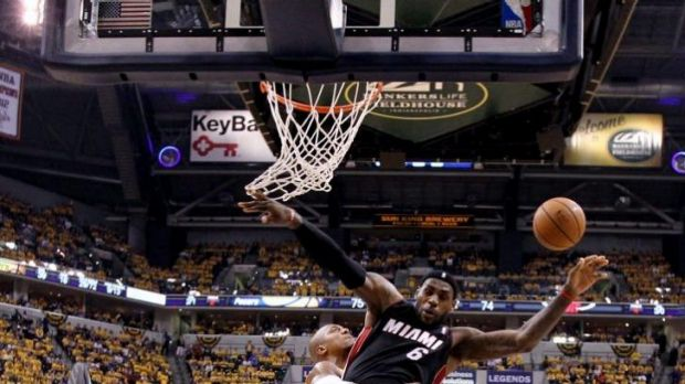 Miami's LeBron James goes to the basket despite the heavy defence of Indiana Pacers forward David West.