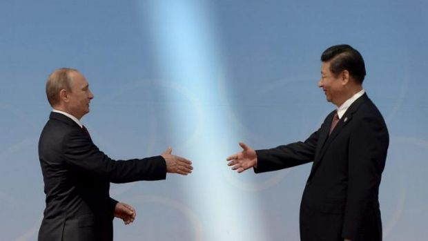 Historic deal: Russian President Vladimir Putin and Chinese President Xi Jinping shake on their gas agreement.