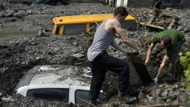The clean up begins ... Residents try to excavate a car trapped in the mud caused by a landslide at the village of ...