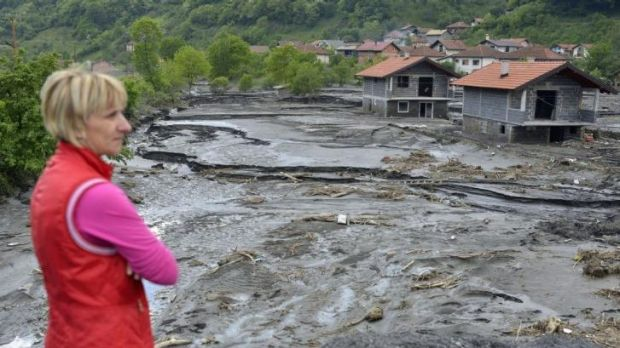 A resident overlooks the damage done by a landslide at the Bosnian village of Topcic Polje. Bosnia, Serbia and Croatia ...