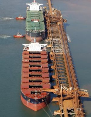 Bulk carriers take on iron ore at a loading facility in Port Hedland.