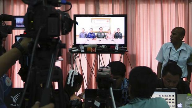 Thai and foreign journalists watch and listen to the announcement of the coup on television at the Army Club's press ...