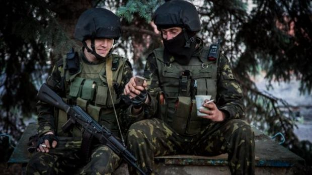 Brief respite ... Ukrainian government soldiers look at a mobile phone while resting at a checkpoint near Slovyansk, Ukraine.
