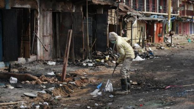 A man cleans up the site of Tuesday's car bomb explosion in Jos, in which 118 people were killed.