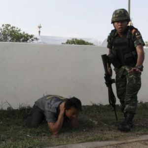 "A man is detained after Thai soldiers entered a pro-government ""red shirt"" camp in Nakhon Pathom province on the ..."