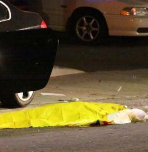 One of the nine crime scenes: A body is covered on the ground after a mass shooting near the campus of the University of ...