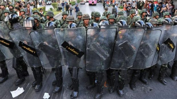 Thai army soldiers stand guard as anti-coup protesters rally nearby in Bangkok.