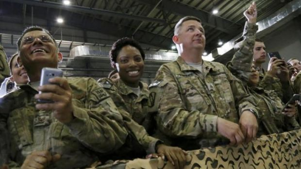 US troops in Afghanistan listen to President Barack Obama during an unannounced visit to Bagram Air Base in Kabul last night.