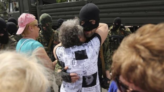 A woman embraces separatist fighters as they parade on the streets of Donetsk near Lenin Square on the day of the ...