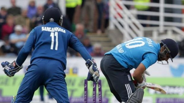 Sri Lanka's Kumar Sangakkara (L) looks on as as England's Ravi Bopara attempts a stroke.