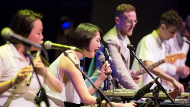 Rainbow Chan (centre) sings, flanked by sister Rose (on flute) and band leader Jonti Danilewitz (with guitar), at the ...