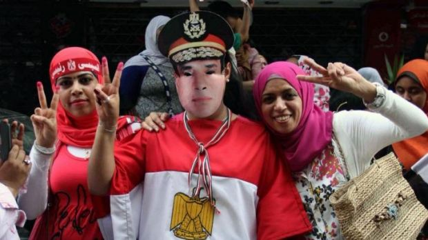 Egyptian supporters of ex-army chief Abdel Fattah al-Sisi, one with a mask bearing his portrait, flash the sign of ...