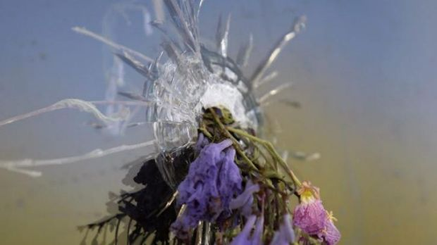 Flowers fill a bullet hole in the windows of the IV Deli in Isla Vista, California.