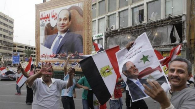 Likely victor ... Supporters of presidential candidate former army chief Abdel-Fattah el-Sissi hold his posters and wave ...