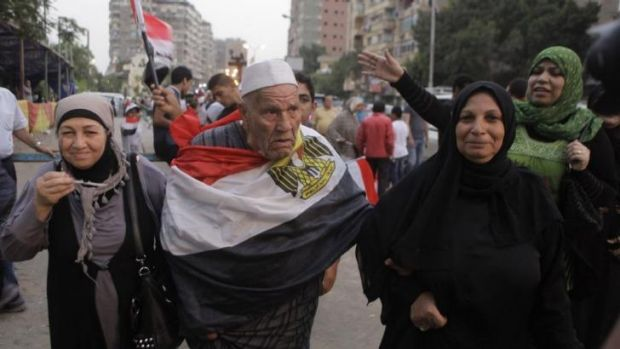 An elderly Egyptian voter covers himself with a national flag as he walks with his family outside a polling centre in ...