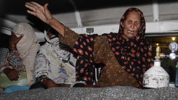 A relative of Farzana Iqbal wails over her body in the back of an ambulance.