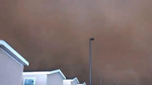 The tornado, filmed by oil worker Dan Yorgason, turns the sky dark.