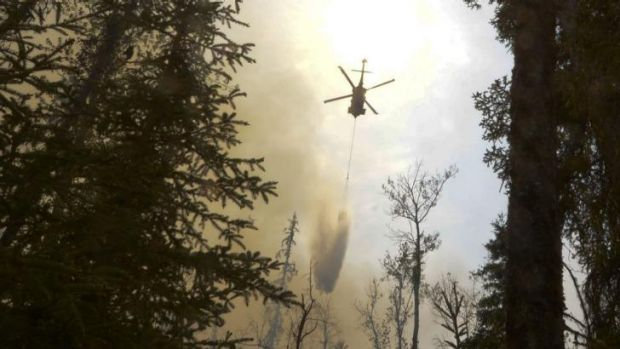 A helicopter dumps water on a portion of the Funny River fire in Alaska