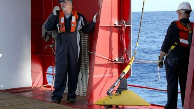Specialists prepare to deploy the towed pinger locator on the Australian vessel Ocean Shield.