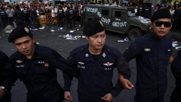 Policemen link arms near a military vehicle vandalised by protesters at Bangkok's Victory Monument on Wednesday.
