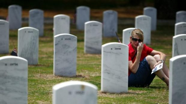 Sami Bolton wipes away tears as she sings to deceased veteran Marcus McLain on Memorial Day at West Tennessee Veterans ...