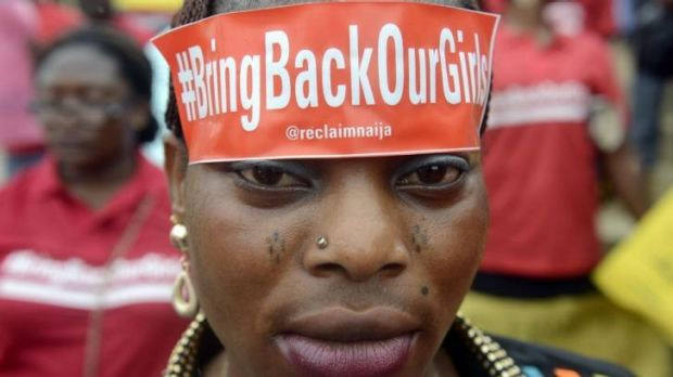 """A woman with a sticker on her head bearing the slogan """"Bring back our girls"""" marches for the release of the more than ..."""