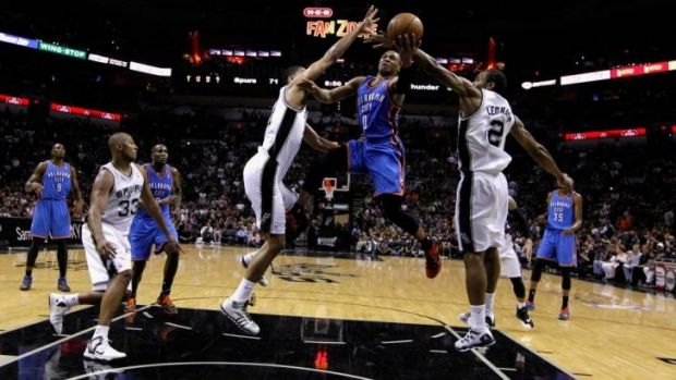 Russell Westbrook of the Oklahoma City Thunder drives to the basket against Tim Duncan and Kawhi Leonard of the San ...