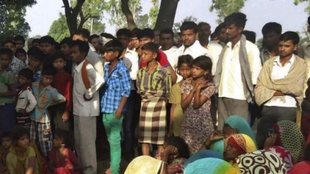 Protest against police ... Indian villagers gather around the bodies of two teenage sisters hanging from a tree in Katra ...