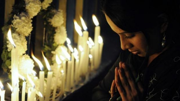 An Indian activist prays as she takes part in a candlelight vigil in Kolkata after the cremation ceremony for a ...