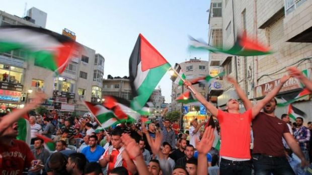 Landmark victory: Palestinian football fans celebrate in the West Bank city of Ramallah.