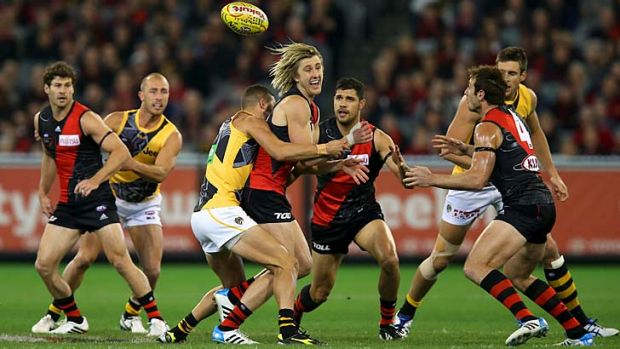 Dyson Heppell handballs under pressure after a centre clearance