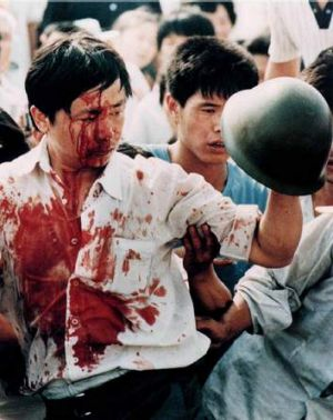 A blood-covered protester holds a soldier's helmet following clashes on Tiananmen Square.