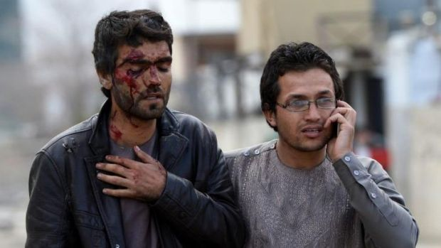 An Afghan man who was injured during an attack on a guesthouse by Taliban gunmen on March 29,  2014 leaves the scene of ...