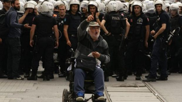 A man protests in front of a police line in Taksim Square.