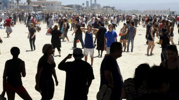 Treasure hunt: people scour the sand at Hermosa Beach in California for the cash.