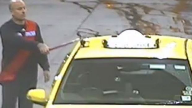 The offender captured on CCTV hittin the taxi with a window-washing squeegee.