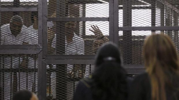 Al Jazeera journalists Mohammed Fahmy, Peter Greste and Baher Mohamed wave to family and friends during their trial in Cairo.