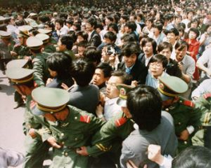 Crowds of students surge through a police cordon before pouring into Tiananmen Square during a pro-democracy ...