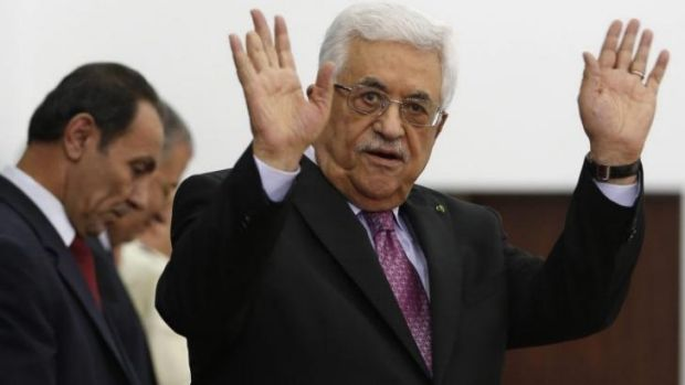 Palestinian President Mahmoud Abbas waves during a swearing-in ceremony of the unity government, in the West Bank city ...