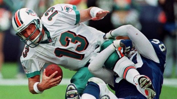 Hard knock ... Miami Dolphins quarterback Dan Marino grimaces as he is sacked by Indianapolis Colts defensive end Mark ...