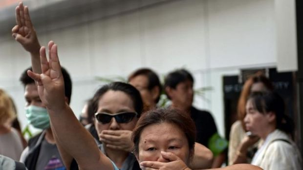 Anti-coup protesters flashing the three-finger salute during a gathering in Bangkok.