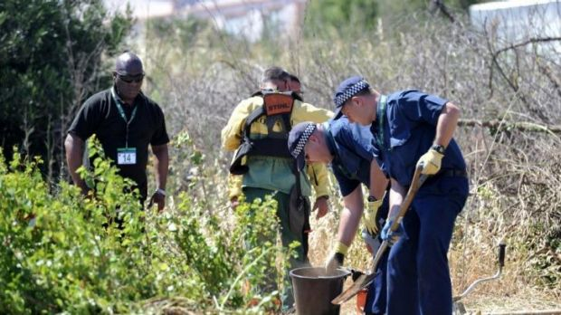 British police officers dig for evidence during the search of an area of scrubland in Portugal.