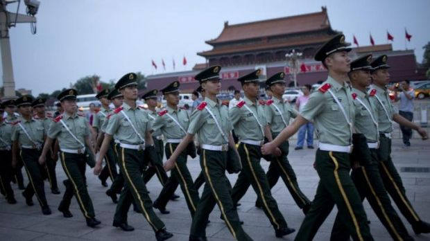 High alert ... Paramilitary policemen march on Tiananmen Square after a flag-lowering ceremony in Beijing.